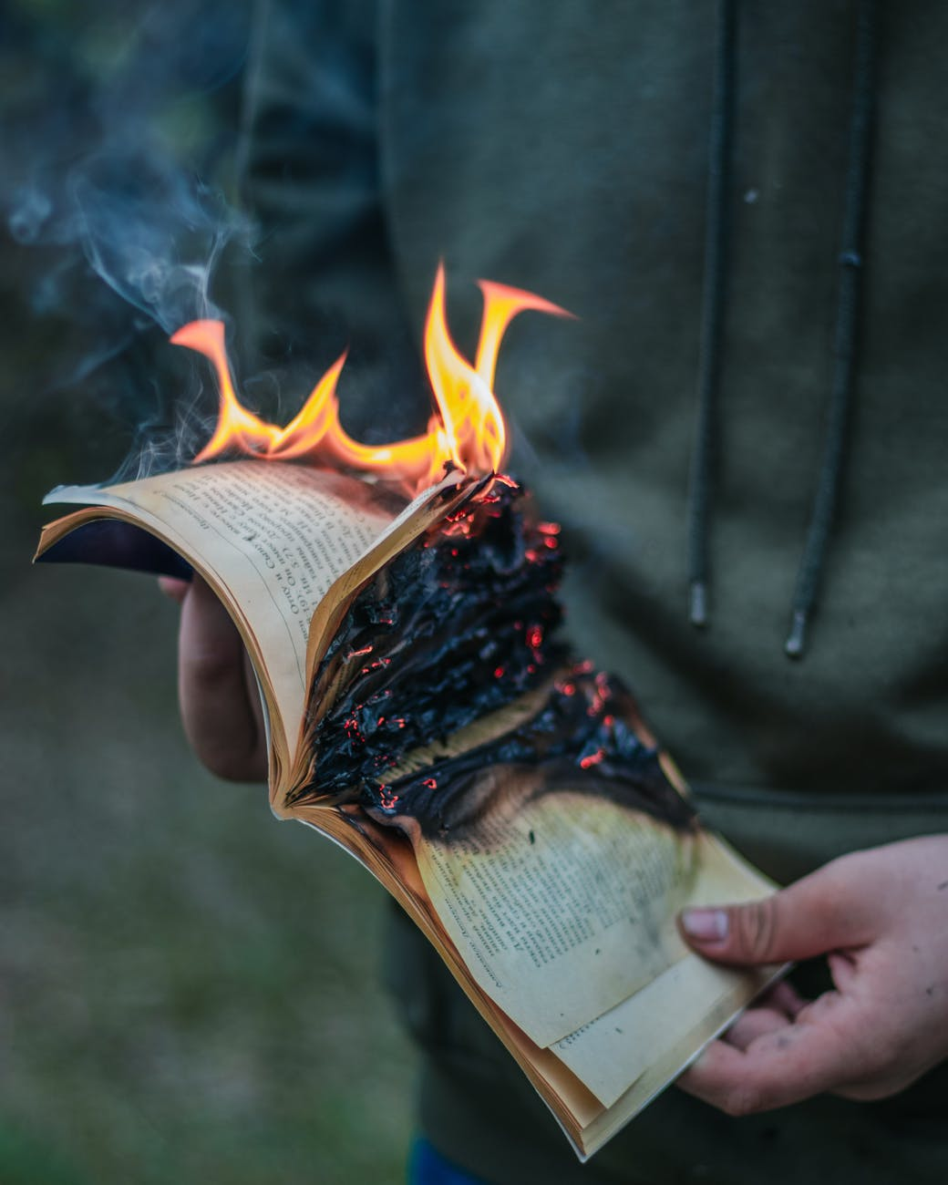 A photo of a person from the shoulders down holding a book that's on fire