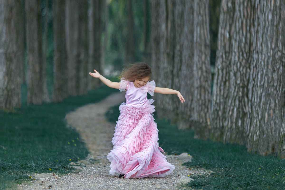 a little girl in a pink ruffled dress standing on a path in a forest, spinning her skirt