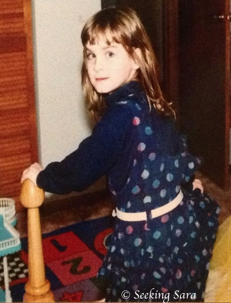 Sara as a 10-year-old, dressed in a blue polkadot dress. Sara is looking over her shoulder at the camera, smiling very faintly.
