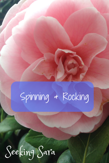 A massive, pink, rose-like flower is central to the photo. Dark green leaves peek out at the bottom of the picture. Texts reads Spinning and Rocking