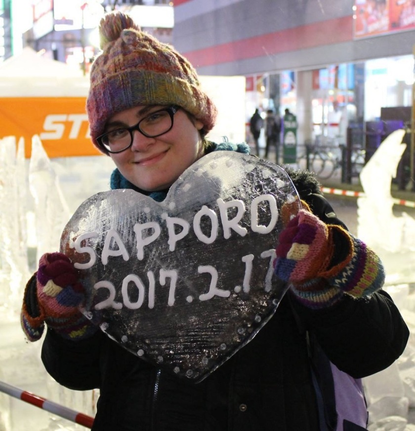 "A photo of Sara in winter gear at the Sapporo Snow Festival holding a heart made out of ice that says, ""Sapporo 2017.2.11""."