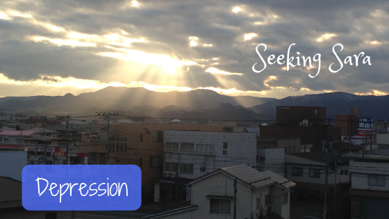 "A dark, cloudy day in Japan. The photo overlooks a small city with many buildings. Off in the distance, rolling mountain ranges cover the horizon. Bright rays of sun are shining through the dark clouds. Text reads ""Depression"""