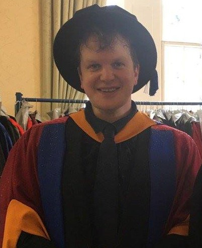 James, a white male with brown hair, dressed in colorful yellow, blue, red, and black graduation robes. He is wearing a black graduation hat.