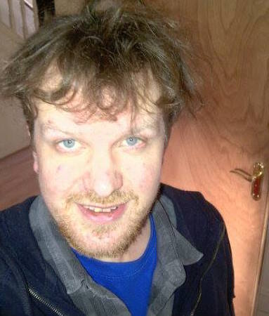A selfie of James, a white man with blue eyes and a beard and mustache. His brown hair is windswept and he wears a blue T-shirt and black jacket. He looks pleased and relieved.