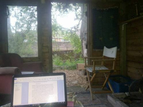 The inside of a rustic cabin, facing the open door to the outside. A computer sits open to James' book open in a Word document.