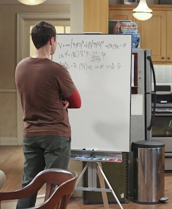 Sheldon Cooper from The Big Band Theory standing with his back to the camera, doing highly complicated math at his whiteboard.