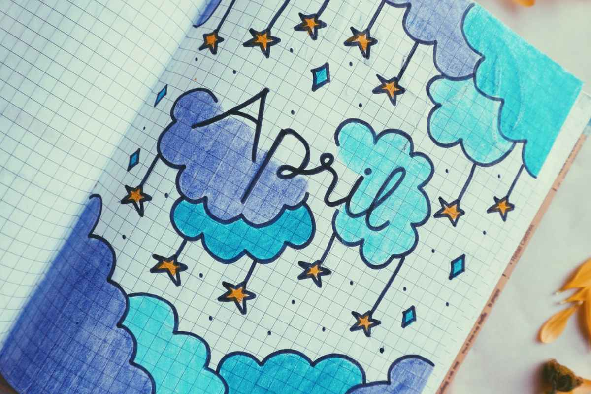 "A photo of a drawn image in a notebook that reads ""April"" surrounded by blue and navy clouds with stars hanging from them."