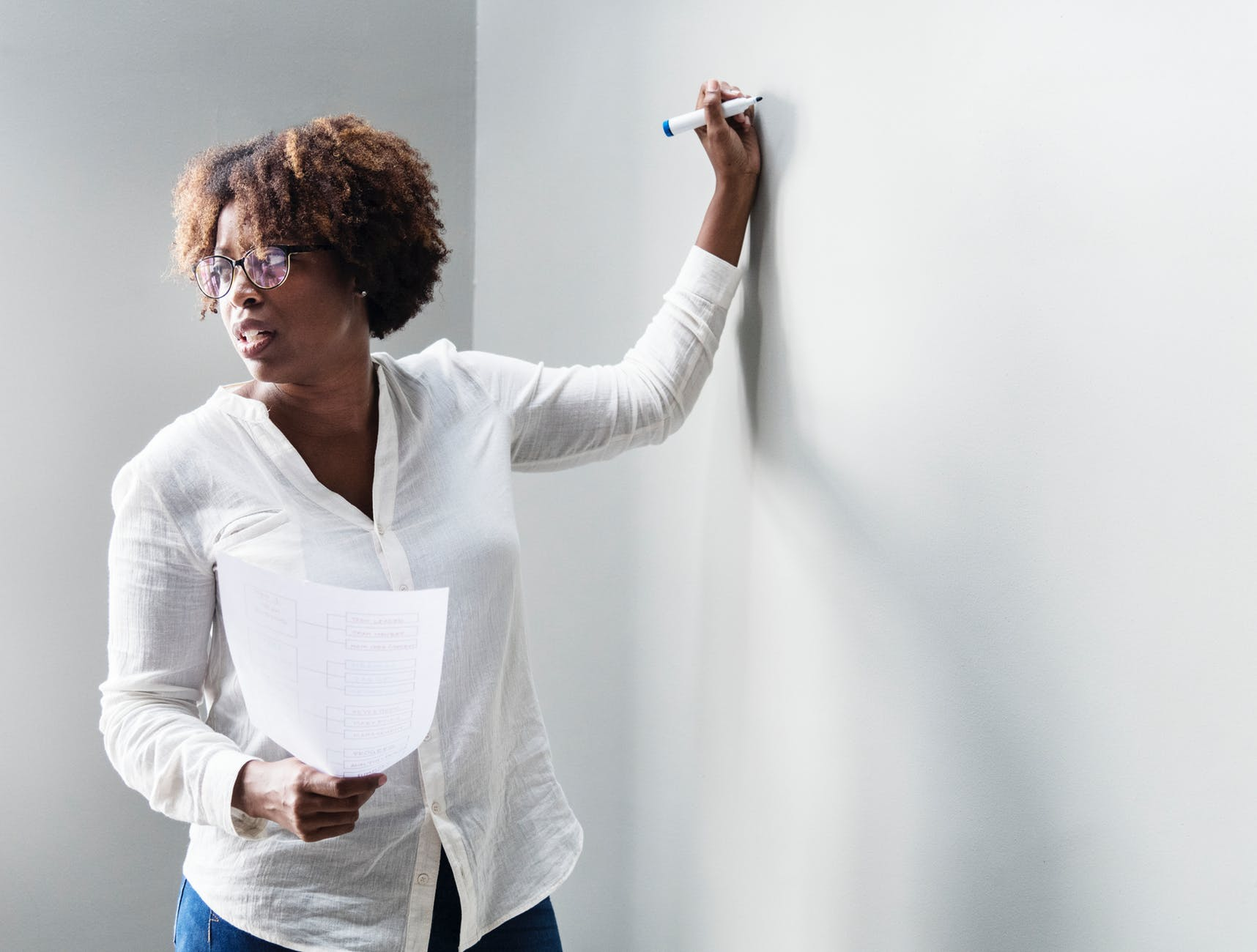 A photo of a black woman with glasses in professional attire, paper in hand, teaching while writing with a marker.