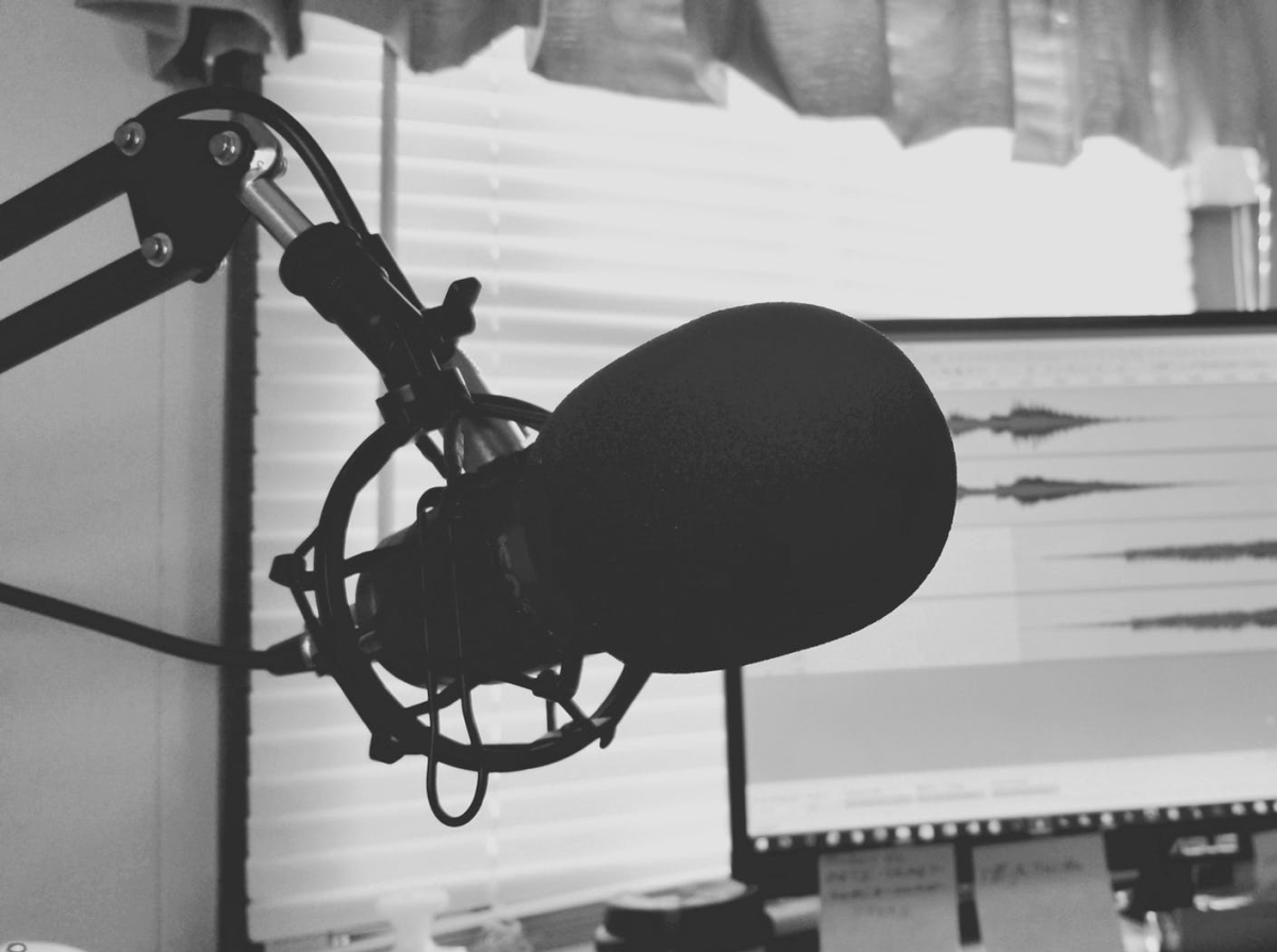 A photo of a podcast microphone pointed at viewer. In the background there is a computer with images of sound bite sound waves.