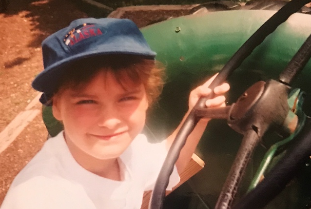 Alex as a young child, sitting on a play tractor, squinting into the sun and smiling faintly at the camera.