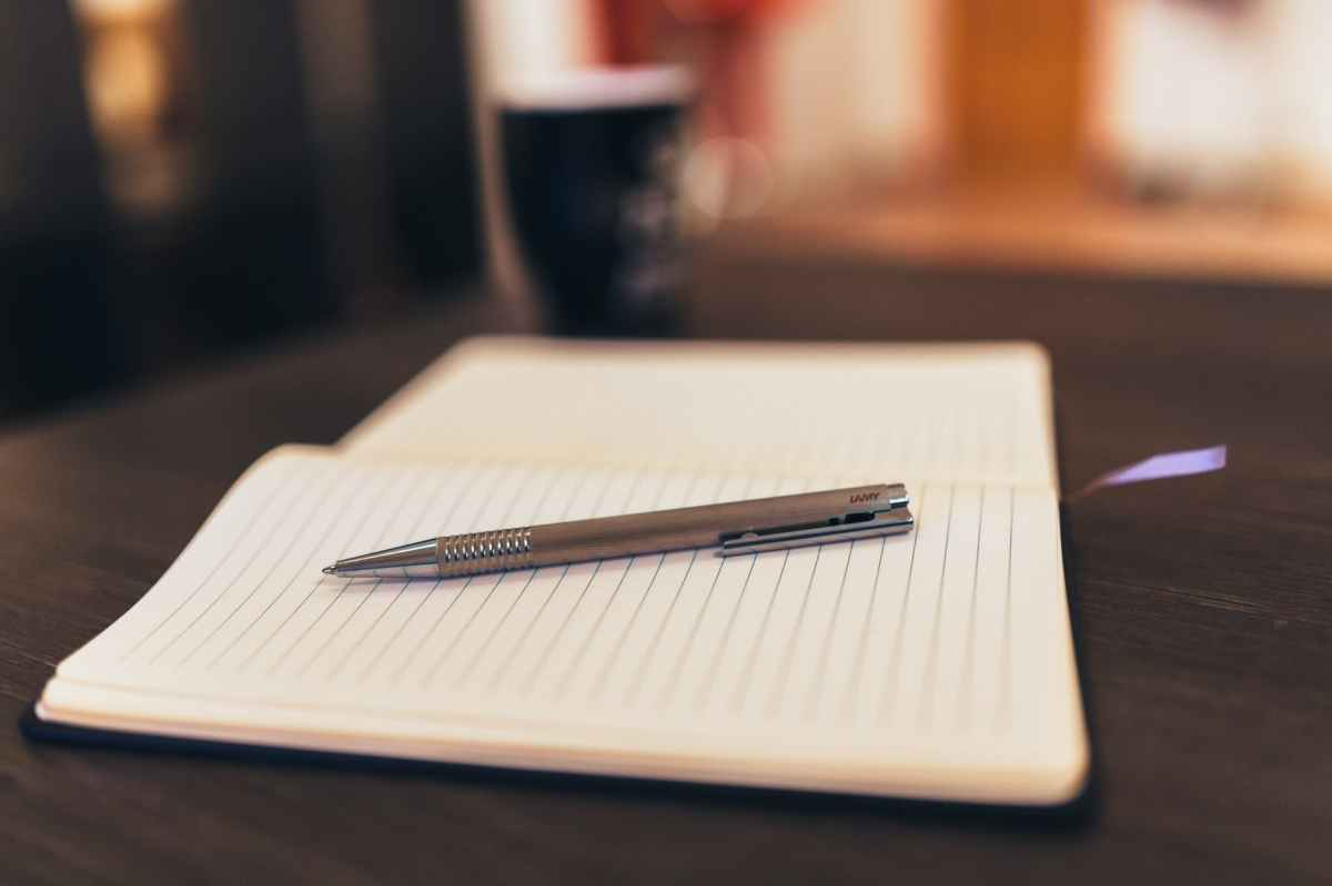 an open notebook sitting on a table with a pen sitting on top